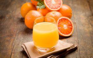Апельсиновый сок и несколько апельсинов