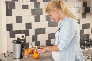 Беременная женщина режет апельсин