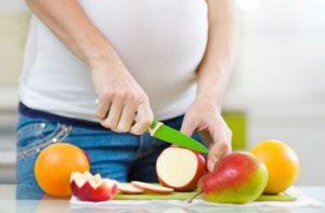 Беременная женщина режет грушу
